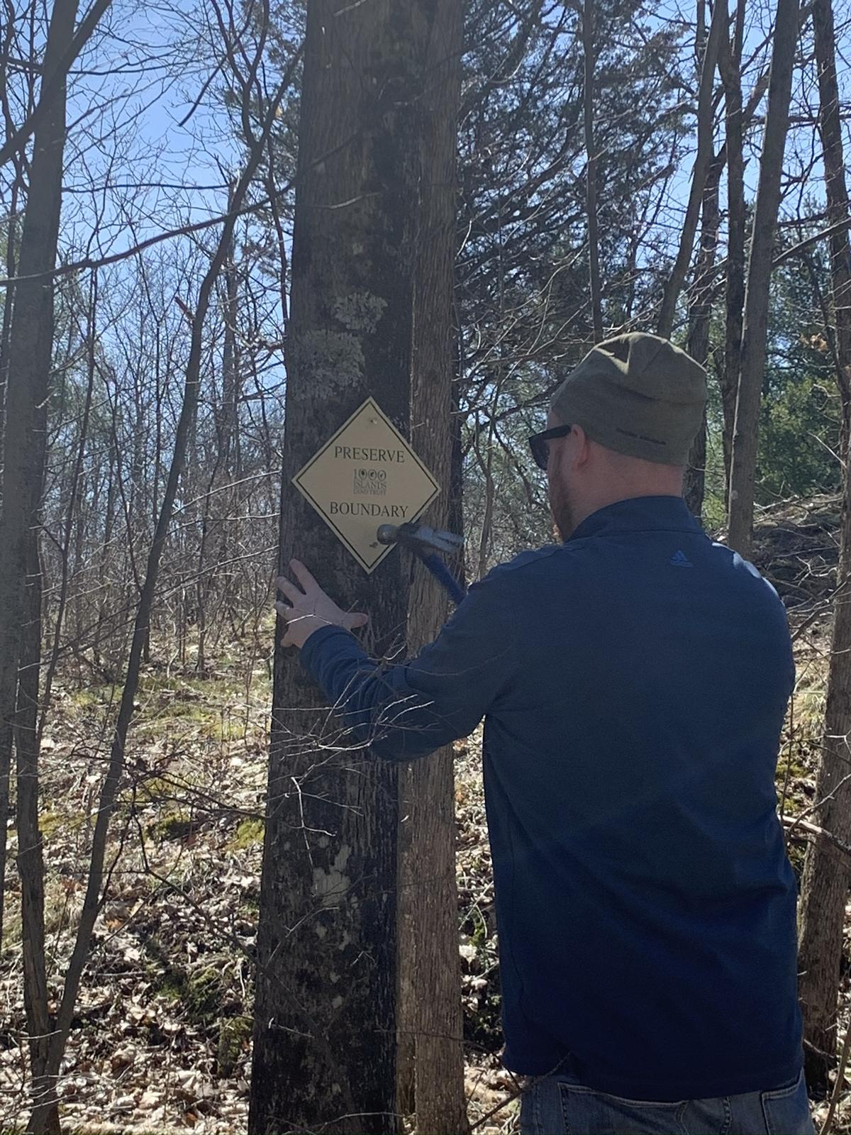 Brandon Hollis, Stewardship Director, marks a preserve boundary, part of the careful stewardship practice that protects conserved lands in perpetuity.